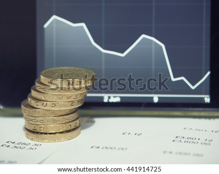 Pound coins on financial figures balance sheet with graph of decreasing exchange rate of the pound sterling. British Pound (GBP) currency after EU referendum result. - stock photo