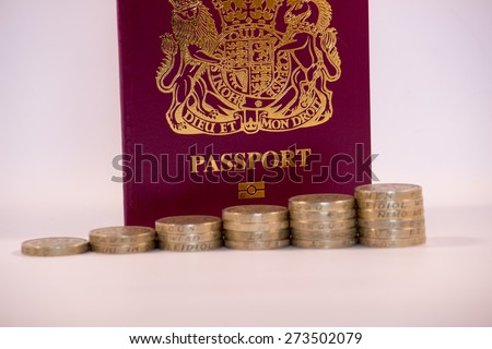 Pound Coins Stacked in front on UK Passport - stock photo