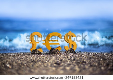 Pound, Euro and Dollar currency icons are standing on the wavy sea side - stock photo