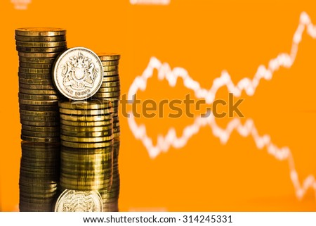 pound GBP coin and gold money. Fluctuating graph on yellow background. Rate of the pound sterling (shallow DOF)  - stock photo