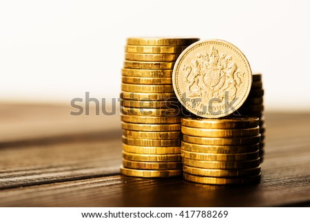 pound GBP coin and gold money on the desk  - stock photo
