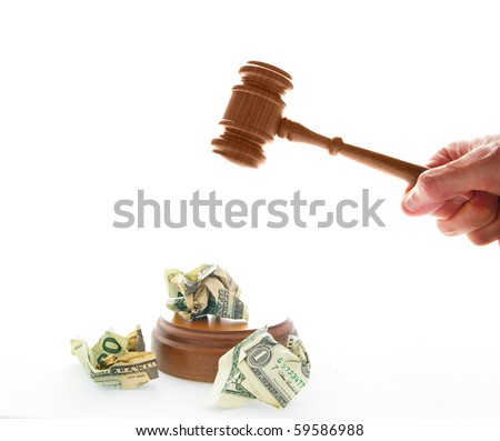 pounding a legal gavel on crumpled cash - stock photo