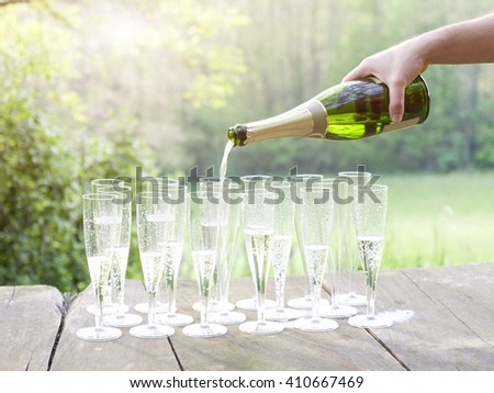 Pour champagne during sunset - stock photo