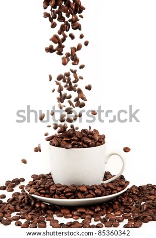 pour coffee grounds into the cup is isolated on a white background - stock photo