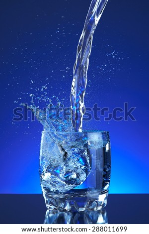 Pour fresh splash water on glass, blue background. Pitcher of water poured into a glass. Image refreshing water that is poured and produces splashes and drops of water. Cool healthy purity beverage.
