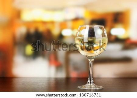 Pour something into glass with drink on wooden table on room background - stock photo