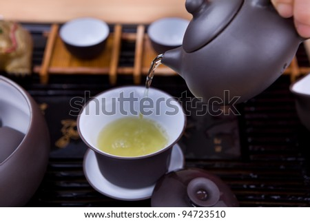 pour tea from teapot Closeup on a brown wood surface. - stock photo