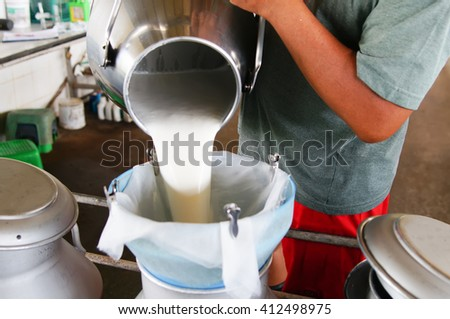 Pour the raw milk into a bucket.                                 - stock photo