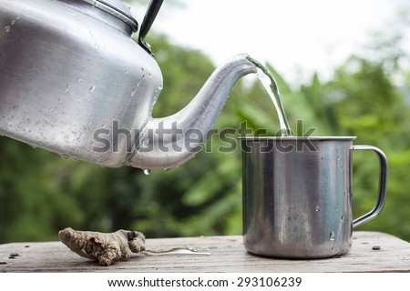 Pour water from aluminium pot  into a stainless steel cup on old wood table With blur green background from a tree soft. - stock photo