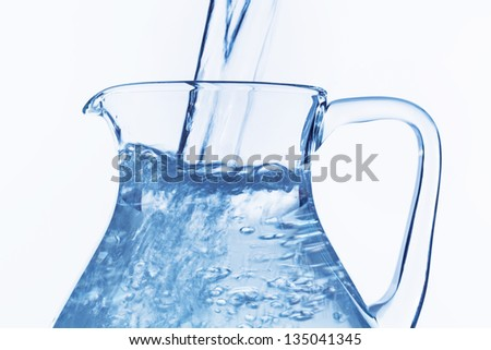 pour water in a carafe, symbol photo for drinking water, refreshments, supplies and consumables - stock photo