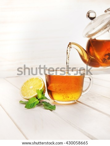 poured from a teapot cup of tea and lemon and mint on a wooden table - stock photo