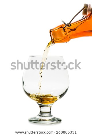 Pouring a glass of brandy from a bottle isolated on a white background - stock photo