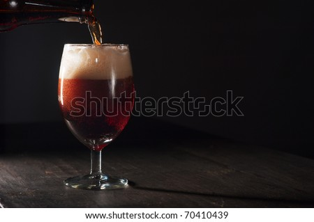 Pouring a glass of brown beer on a rough wooden table - stock photo