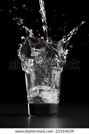 Pouring a glass of water, water splashing out of the glass, against a black background