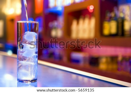 pouring a glass with ice cubes - stock photo