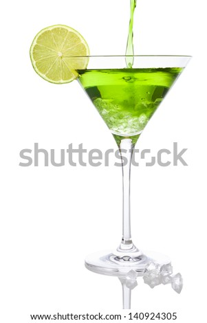 Pouring a green liquid into a Martini glass with lime slice and crushed ice, isolated on white background - stock photo