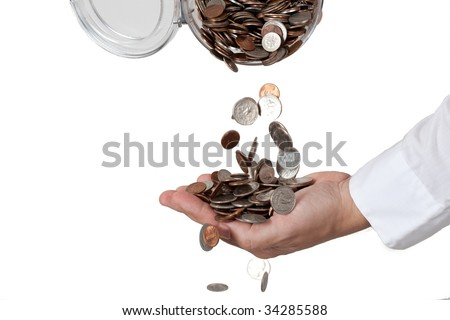 Pouring a lot of change (coins) from the jar into a hand. Isolated against white background. - stock photo