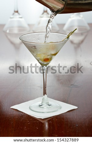 pouring a martini into  a chilled glass over a black background - stock photo