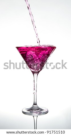 pouring a pink cocktail on white  background