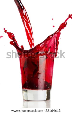Pouring a red beverage into a clear glass - stock photo