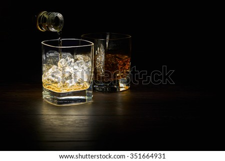 Pouring a Single Malt Whiskey in a glass on a wooden table top. - stock photo