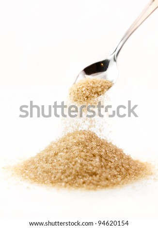 Pouring a tablespoon of brown sugar onto a pile of sugar. - stock photo