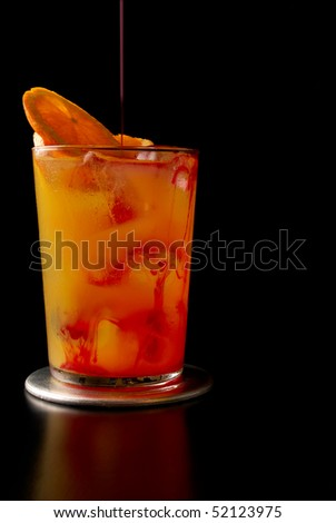 Pouring a tequila sunrise cocktail - stock photo