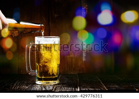 Pouring beer from bottle into glass on wood table at bar and bokeh light with copy space. - stock photo