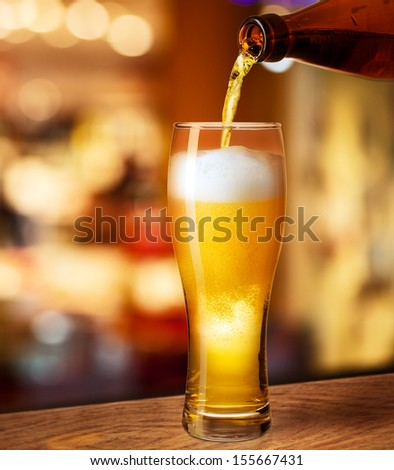 pouring beer in glass on bar or pub desk - stock photo