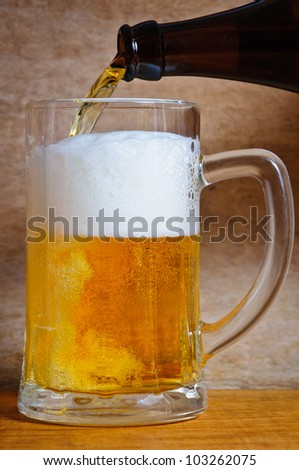 Pouring beer in mug on vintage background