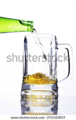 Pouring beer into a glass for international beer days - stock photo