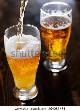 pouring beer into a tall mug on slate table - stock photo