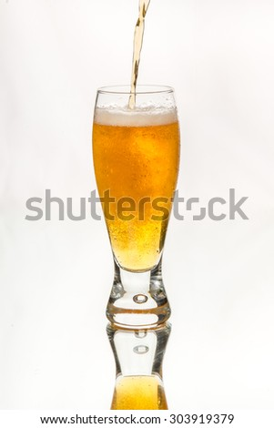 Pouring beer into glass. Cold, unfiltered golden ale. On glass table, isolated in white background. Cold beer with condensed water on glass.. Craft beer. - stock photo