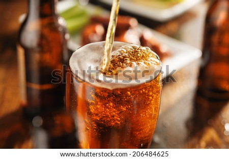 pouring beer into glass with bbq chicken wings in background - stock photo