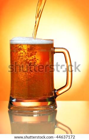 Pouring beer into mug over orange background - stock photo