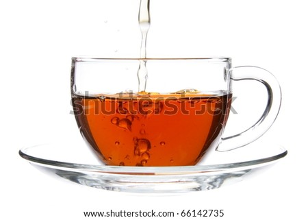 Pouring Black Tea into Cup with Splash Isolated - stock photo