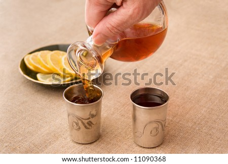 pouring brandy into the silver drinking vessels from glass decanter - stock photo