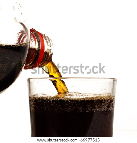 pouring brown refreshment on glass on white - stock photo