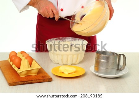 Pouring cake batter into baking pan. Making bundt cake with chocolate glaze. - stock photo