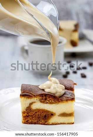Pouring caramel sauce on piece of toffee and vanilla cake - stock photo