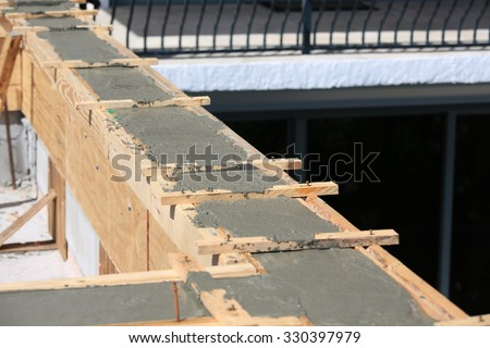 Pouring cement for a tie beam on a concrete block wall.  The cement is now setting up to dry. - stock photo