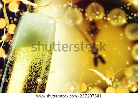 Pouring champagne against holiday lights and clock close to midnight. - stock photo