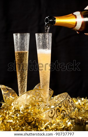 Pouring champagne in two crystal glasses with festive gold decorations and black background