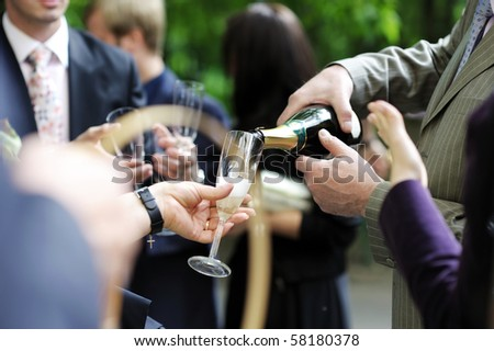 Pouring champagne into a glass on a wedding celebration - stock photo