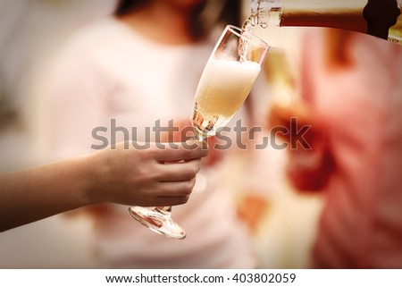 Pouring champagne into glass at hen-party, close up - stock photo