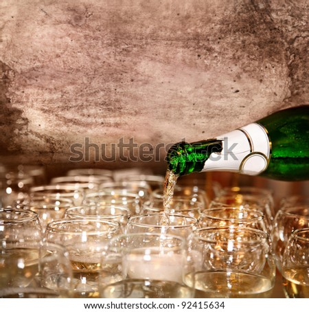 Pouring Champagne to the glasses in restaurant at vintage textured background. Represents party. Free space for your text - stock photo