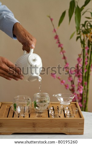 Pouring chinese green tea into glass teapot - stock photo