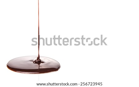 Pouring chocolate syrup over white background