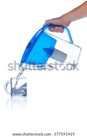 Pouring clean water from water filter pitcher - stock photo
