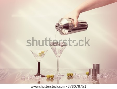 Pouring cocktail drink from a shaker into Art Deco cocktail glasses